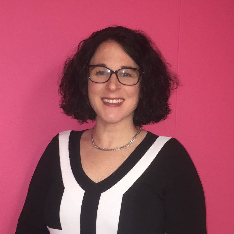 A woman smiling in front of a pink wall